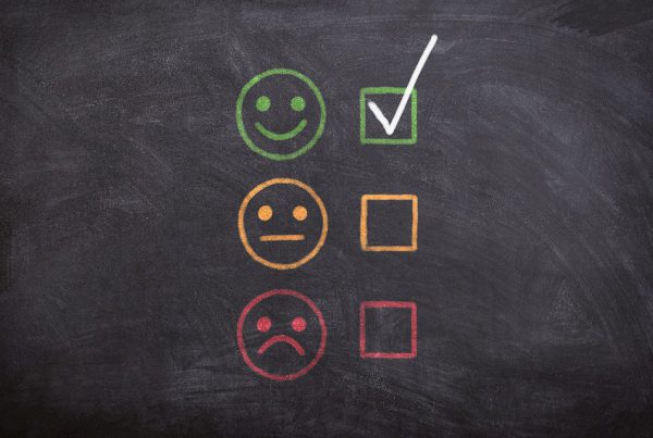 Blackboard with a column of smiley faces: happy, neutral, sad.
